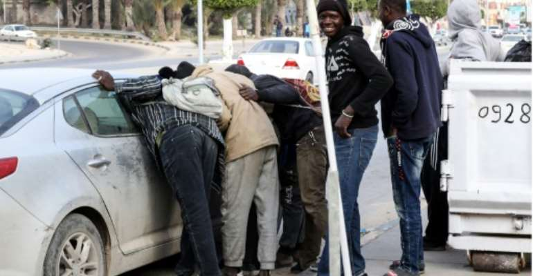African casual labourers clamour for odds jobs from the occupant of a car in Libya's capital Tripoli.  By Mahmud TURKIA (AFP)