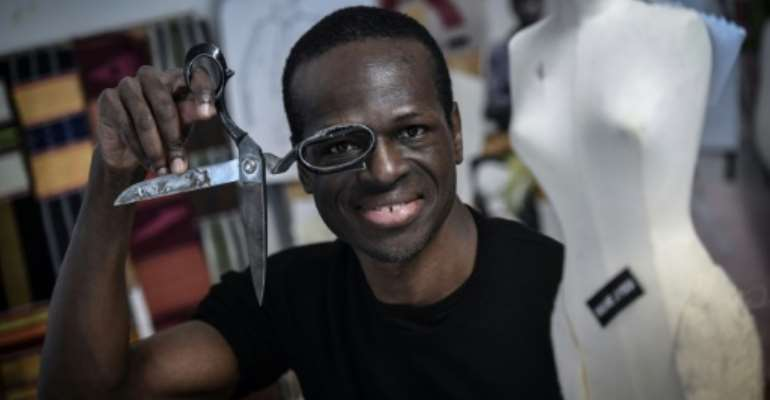 African first: Cameroon-born fashion designer Imane Ayissi at work in his Paris studio.  By STEPHANE DE SAKUTIN (AFP)