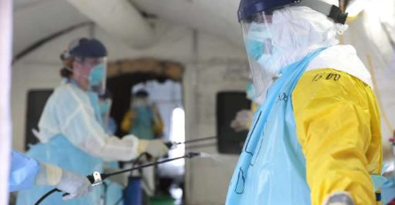 Medical workers spray their protective gear at an Ebola treatment centre in Monrovia on December 19, 2014.  By Evan Schneider (UN/AFP/File)