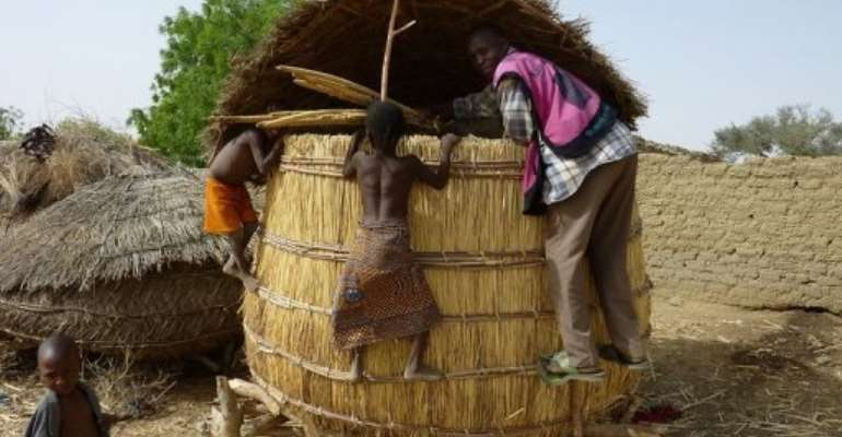 Children from the Tarna village climb on a grain silo in southern Niger in 2010.  By Boureima Hama (AFP/File)
