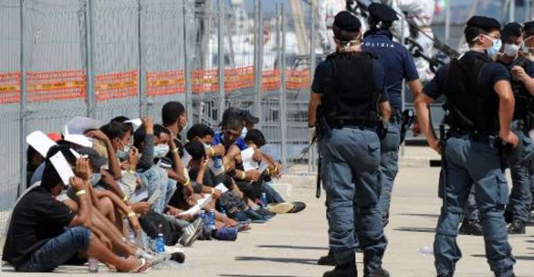 Immigrants wait after disembarking from an Italian military ship on August 11, 2014 in the port of Reggio Calabria, southern Italy, following Mare Nostrum rescue operations at sea.  By Giovanni Isolino (AFP/File)
