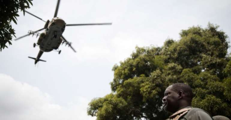 Air support: Prime Minister Firmin Ngrebada salutes the troops on January 10 as a Russian military helicopter flies overhead.  By FLORENT VERGNES (AFP)
