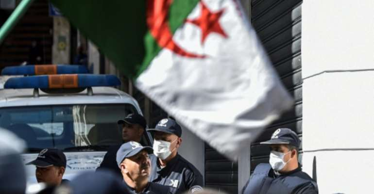 Algerian police wearing face masks stand as protesters march past during an anti-government demonstration in the capital Algiers on March 6.  By RYAD KRAMDI (AFP/File)