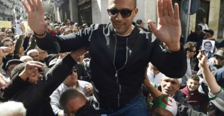 Algerian protesters carry journalist Khaled Drareni, who was arrested while covering an anti-government protest and was accused of