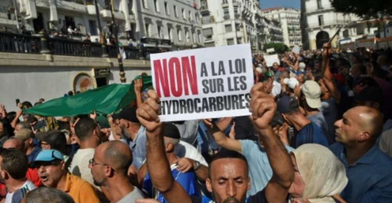 Algerian protesters chant anti-government slogans near the parliament building in Algiers on October 13, 2019 against the military's role in politics and a draft energy law.  By RYAD KRAMDI (AFP)