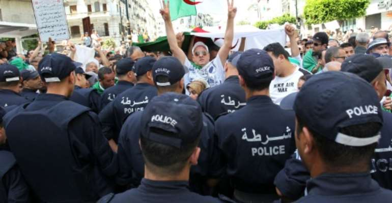 Algerian protesters face riot police during a demonstration in the capital Algiers in June.  By - (AFP)