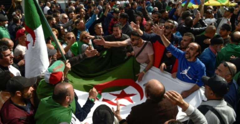 Algerian protesters gathered during a weekly anti-government demonstration in the capital Algiers on March 13 before the coronavirus outbreak halted such rallies.  By RYAD KRAMDI (AFP/File)
