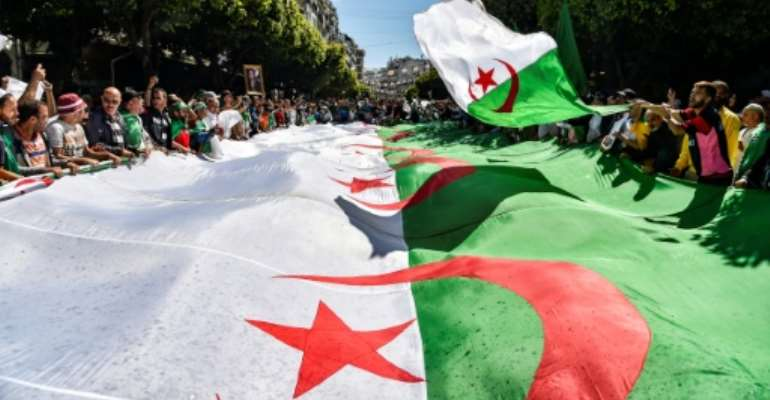 Algerian protesters march with a giant national flag during a demonstration in the capital Algiers on May 31, 2019.  By RYAD KRAMDI (AFP/File)