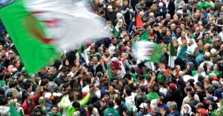 Algerian protesters wave national flags during an anti-government demonstration in the capital Algiers.  By RYAD KRAMDI (AFP)
