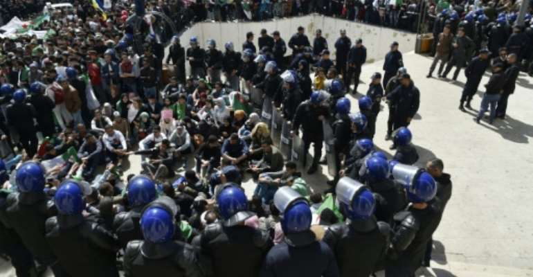 Algerian riot police come face to face with anti-government protesters in the capital Algiers.  By RYAD KRAMDI (AFP)