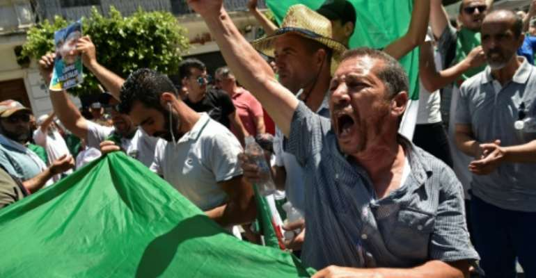 Algerians -- seen here carrying the national flag -- protested against the authorities for a nineteenth consecutive week on Friday.  By RYAD KRAMDI (AFP)