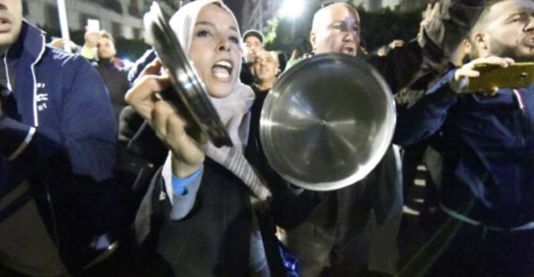 Algerians bang on pots and pans as they protest against the December 12 presidential election they say will cement in power a political elite rejected by the people.  By RYAD KRAMDI (AFP)