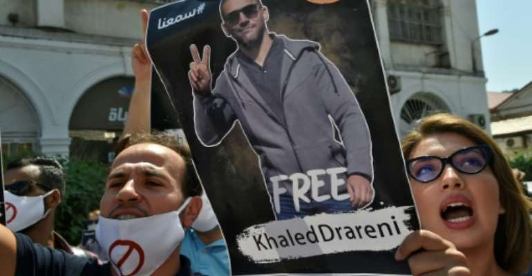 Algerians brandish a picture of journalist Khaled Drareni during a rally to protest his three-year jail term handed down after being convicted in August of charges of 'inciting an unarmed gathering'.  By RYAD KRAMDI (AFP)