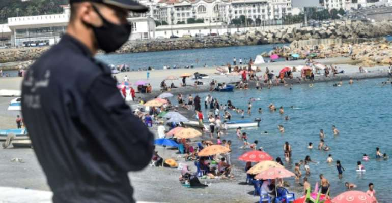 Algerians throng a beach in the Bab el-Oued suburb of the capital Algiers after authorities reopened beaches for the first time following a five-month coronavirus lockdown.  By RYAD KRAMDI (AFP)
