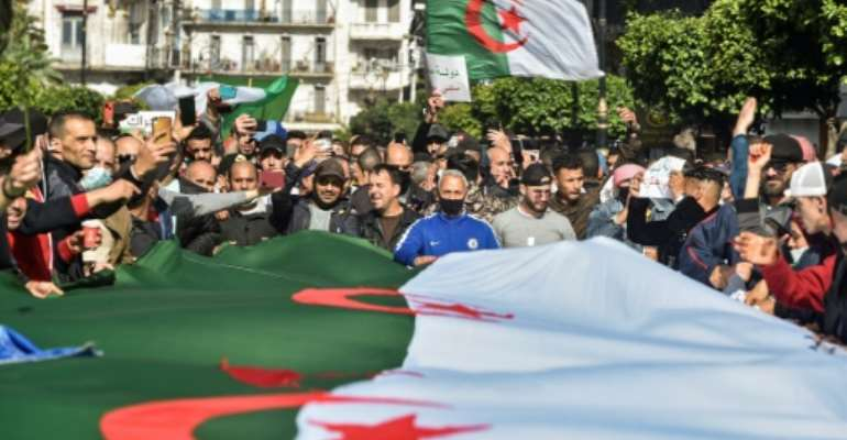 Algerians wave national flags during an anti-government protest in the capital Algiers on Friday.  By RYAD KRAMDI (AFP)