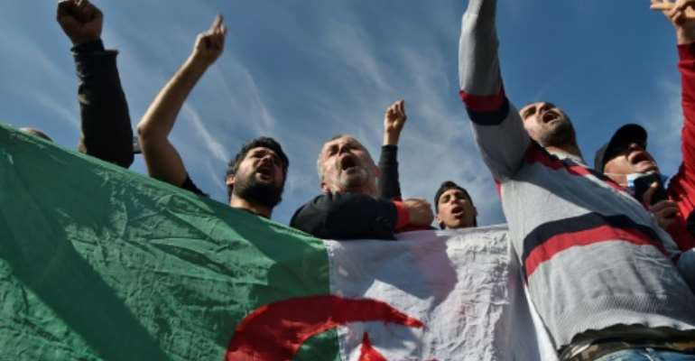 Algerians waving flags gathered outside the Kolea prison on Friday to await activists expected to be freed under a presidential pardon.  By RYAD KRAMDI (AFP)