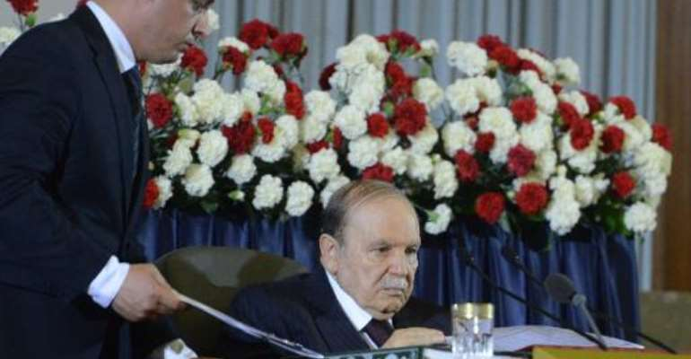An officials hands Algerian President Abdelaziz Bouteflika documents during his inauguration ceremony as he is sworn in for a fourth term in Algiers on April 28, 2014.  By Farouk Batiche (AFP/File)