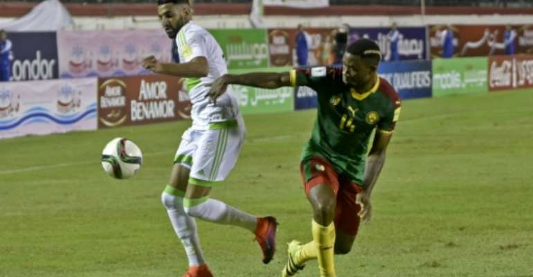 Algeria's Riyad Mahrez (L) fights for the ball with Cameroon's Aurelien Chedjou during their FIFA World Cup 2018 qualifying match at Stade Tchakert in Blida, on October 9, 2016.  By RYAD KRAMDI (AFP/File)