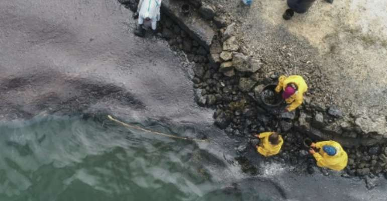 All-hands emergency: People scoop up oil at Bambous Virieux beach.  By - (L'Express Maurice/AFP)