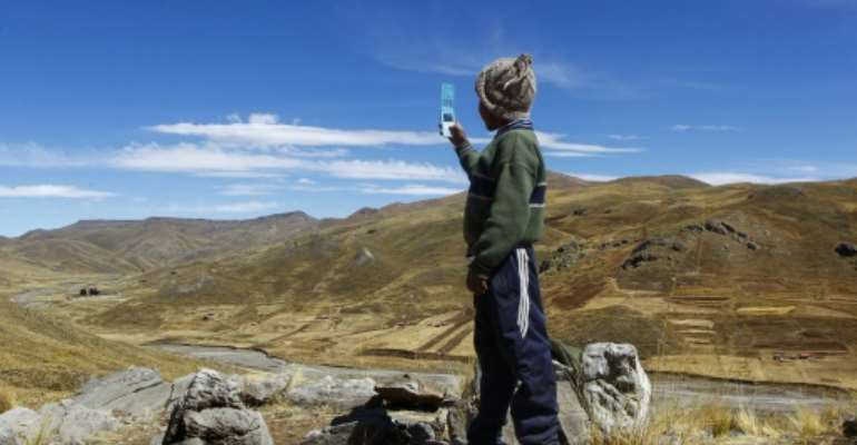 Alvaro Cabrera, 10, searches for a cellphone signal atop a hill near Manazo, Peru while trying to take part in a virtual class; the UN says Covid-19 and school closures have left millions of children worldwide unable to access distance education.  By Carlos MAMANI (AFP/File)