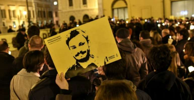 Amnesty International activists  hold a picture of student Giulio Regeni who was murdered in Egypt as they take part in a demonstration in front of the Italian Parliament in Rome in January 2017 a year after his killing.  By ANDREAS SOLARO (AFP/File)