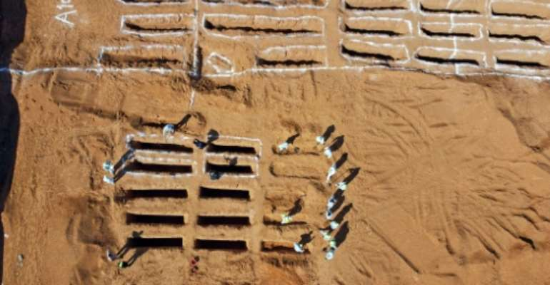 An aerial view shows Libyan experts exhuming human remains from mass graves in Tarhuna, southeast of the capital Tripoli, in this file picture taken on October 28, 2020.  By Mahmud TURKIA (AFP/File)