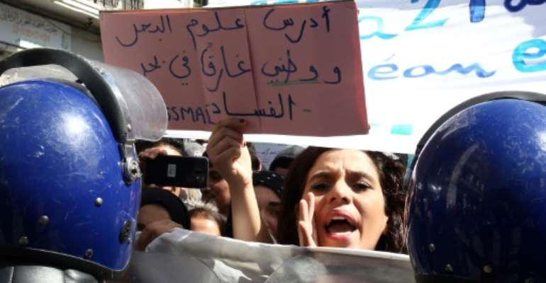 An Algerian protester holds sign that reads