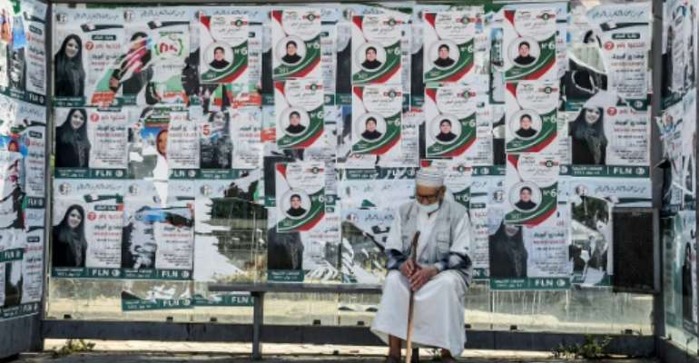 An Algerian sits in front of campaign posters in the capital Algiers on Friday, a day before legislative elections.  By RYAD KRAMDI (AFP)