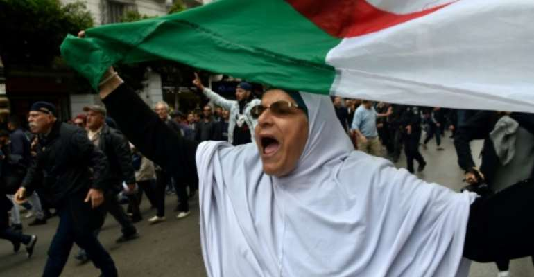 An Algerian woman waves a national flag during an  anti-government demonstration in the capital Algiers on March 14, 2020.  By RYAD KRAMDI (AFP/File)