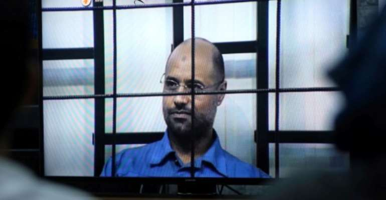 An armed group in Libya said on Facebook on June 10, 2017, it has freed Seif al-Islam who has been in custody since November 2011, pictured in 2014 answwering judges' questions in Tripoli.  By MAHMUD TURKIA (AFP/File)