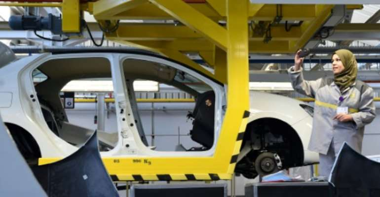 An employee of French carmaker Renault group takes a picture of a car in production  at a plant, in the south of the Algerian city of Oran.  By Farouk Batiche (AFP/File)