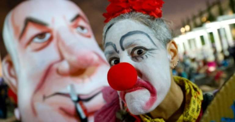 An Israeli woman in a clown outfit mocks a giant head costume representing Prime Minister Benjamin Netanyahu as she takes part in a demonstration in Tel Aviv against the government and an imminent and unprecedented second nationwide virus lockdown.  By JACK GUEZ (AFP)