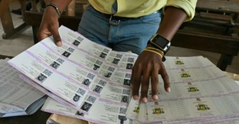 An Ivory Coast Electoral Commission official in Abidjan helps out with distribution of voting cards on October 14, 2020 ahead of the country's presidential election.  By Issouf SANOGO (AFP/File)