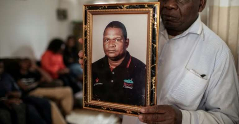 Anastacio Matavele, seen here in a portrait held by a family representative, was killed in the run-up to Mozambique's October election.  By GIANLUIGI GUERCIA (AFP)