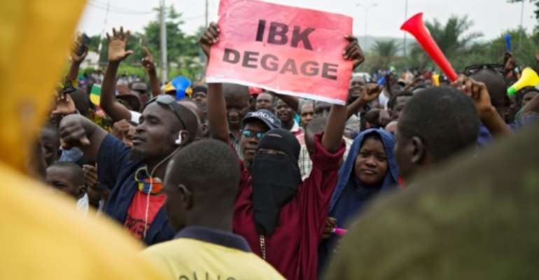 Anger: A demonstrator holds up a sign reading 'IBK out,' referring to President Ibrahim Boubacar Keita by his initials, in a protest in Bamako on August 11.  By ANNIE RISEMBERG (AFP)