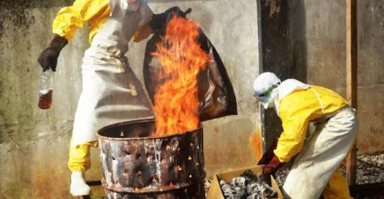 Health workers burn used protective gear at the Medecins Sans Frontieres center in Conakry on September 13, 2014.  By Cellou Binani (AFP/File)