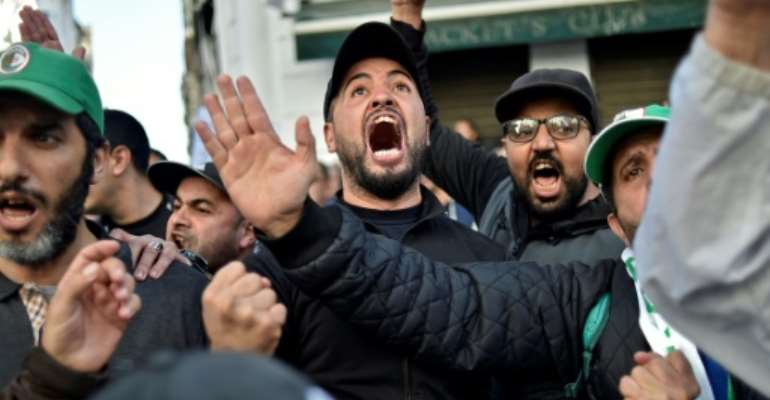 Anti-government protesters in Algiers yell slogans against next month's presidential election on November 29, 2019.  By RYAD KRAMDI (AFP)