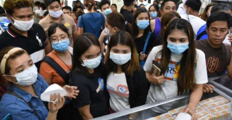 Anxious shoppers try to buy face masks in Manila after the first foreign fatality from the new coronavirus was reported  in the Philippines.  By Ted ALJIBE (AFP)