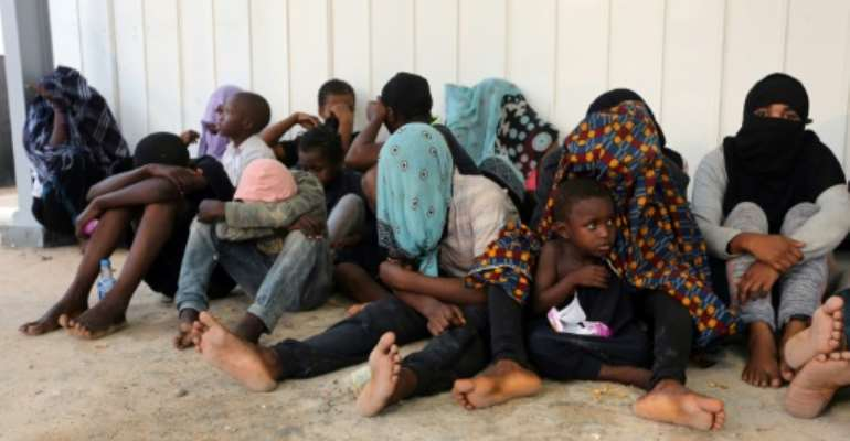 Arab and African migrants gather at a naval base in the Libyan capital Tripoli on September 27, 2017, after they were rescued by the coastguards off the Libyan coast.  By MAHMUD TURKIA (AFP/File)