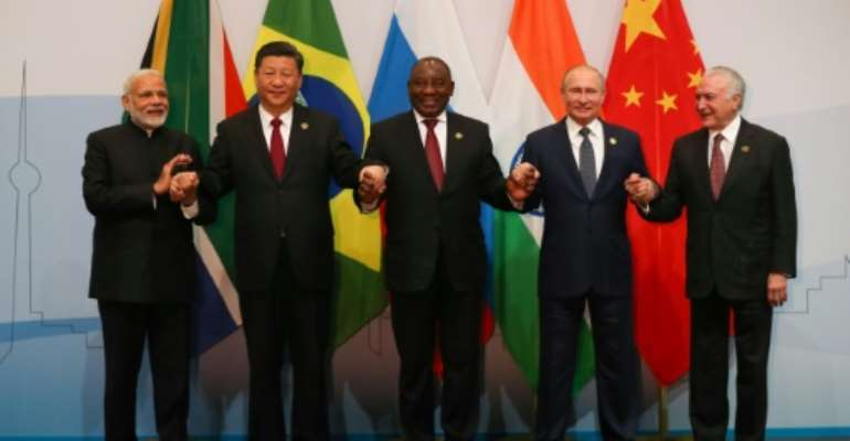Arm in arm: Indian Prime Minister Narendra Modi, Chinese President Xi Jinping, South African President Cyril Ramaphosa, Russian President Vladimir Putin and President Michel Temer of Brazil.  By MIKE HUTCHINGS (POOL/AFP)