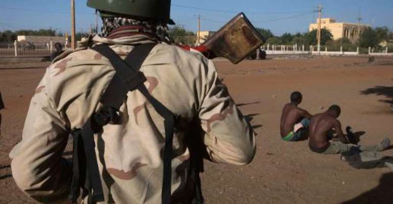 A Malian soldier (left) checks two suspected MUJAO fighters arrested in the central market in Gao on February 22, 2013.  By Joel Saget (AFP/File)
