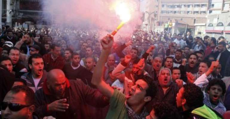 A fan of al-Masry football club waves a flare outside the prison in the city of Port Said on January 25, 2013.  By  (AFP)