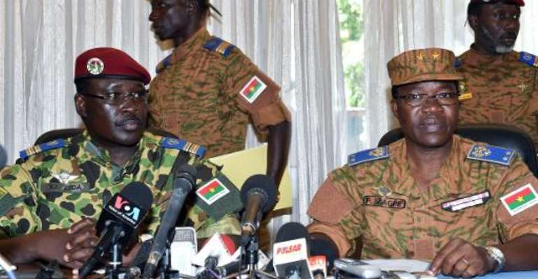 Burkina Faso's Lieutenant-Colonel Yacouba Isaac Zida (L) listens as Burkina Faso's General Pingrenoma Zagre (R) reads a statement at the end of a meeting with military commanders on November 1, 2014 in Ouagadougou.  By Issouf Sanogo (AFP)