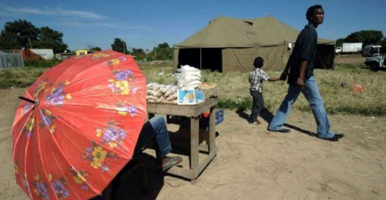 Zimbabweans walk past a tent used as a polling station in Mbare township on March 17, 2013.  By Alexander Joe (AFP)