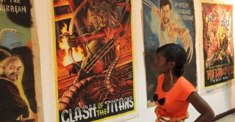 A visitor looks at film posters drawn by local Ghanaian artists during an exhibition in Accra, Ghana, on March 20, 2014.  By Chris Stein (AFP)