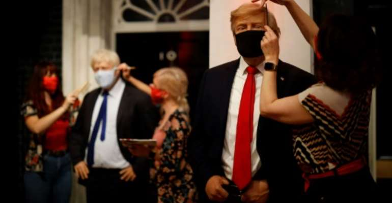 Artists at London's Madame Tussauds check the masks on the wax figures of British PM Boris Johnson and US President Donald Trump.  By Tolga Akmen (AFP)