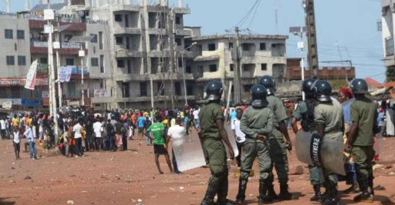 Demonstrators face riot police in Conakry on November 16, 2013.  By Cellou Binani (AFP/File)