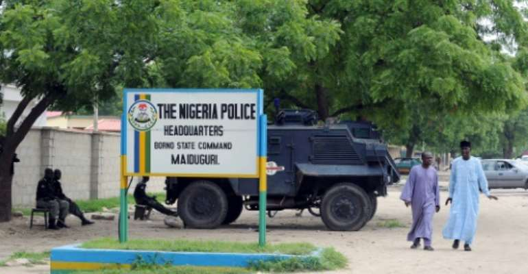 People walk past police armoured tank stationed at the main gate of the state police command headquaters in Maiduguri, Borno State.  By Pius Utomi Ekpei (AFP/File)