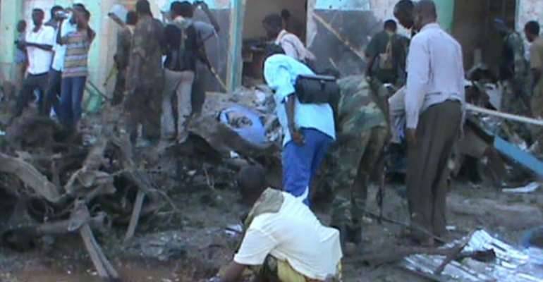 People and soldiers search in the rubble of a destroyed building on  February 28, 2016 in Baidoa after twin explosions in the Somali city killed at least 30 people.  By - (AFP)