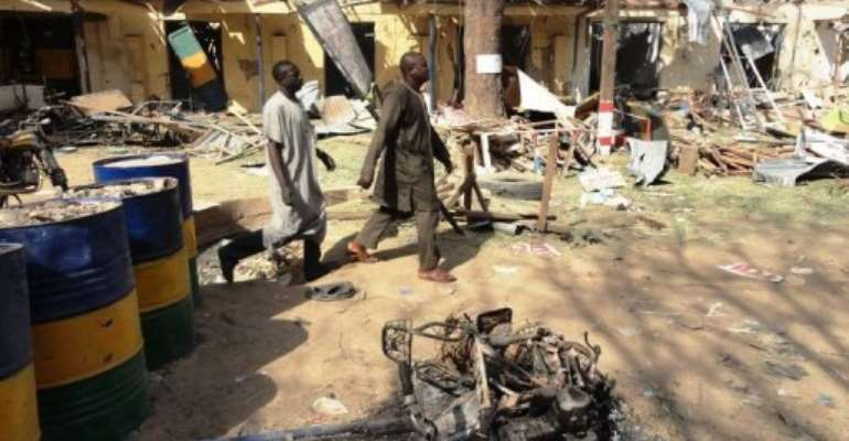 Two residents pass by bombed corner shops attached to Bompai police barracks in Kano in January.  By Aminu Abubakar (AFP/File)